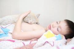 Sonno del ragazzo con il gatto, l'animale domestico favorito che si trovano sul petto del bambino, le interazioni fra i bambini e Fotografie Stock Libere da Diritti
