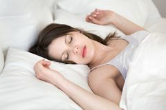 Sonno di rilassamento della giovane donna nel letto bianco accogliente immagini stock