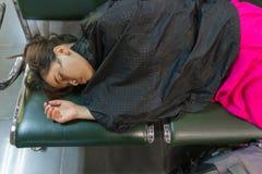 Sonno femminile asiatico esaurito all'aeroporto Fotografie Stock Libere da Diritti