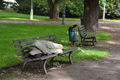 Sonno senza casa su un banco di sosta Fotografia Stock
