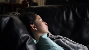 Sonno solo malato della donna asiatica al sofà con il video generale stock footage
