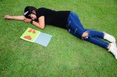 Sonno sveglio della ragazza e vedere cuore rosso sul libro Fotografia Stock