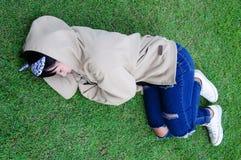 Sonno sveglio della ragazza su erba nel giardino Fotografie Stock Libere da Diritti