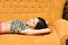 Sonno teenager della ragazza sul sofà Fotografie Stock Libere da Diritti