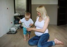 Sonny измеряет размер живота беременной матери Стоковые Фото
