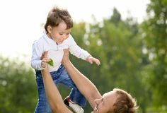 Sonny. Happy father throws in the sky small son royalty free stock image