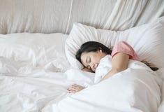 Sono asi?tico da mulher do close up na cama sob a cobertura no fundo do quarto na manh? foto de stock