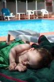 Sono bonito do bebê em um banco com toalhas fotos de stock