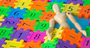 Sono de madeira do fantoche no número plástico colorido no fundo azul Conceito da matemática ou do cálculo da educação Copie o es Foto de Stock