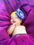 Sono de sorriso do bebê recém-nascido no roxo ultravioleta da cama fotografia de stock royalty free