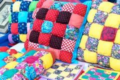 Sono i cuscini, i potholders, involucri sono fatti a mano Vari modelli sotto forma di cellule, quadrati delle combinazioni di col Fotografie Stock