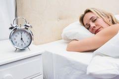 Sono louro bonito na cama com despertador Fotografia de Stock