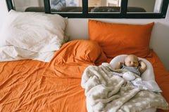 Sono saudável do dia para o recém-nascido Uma criança dorme no casulo ortopédico do bebê em uma cama maior na sala dos pais fotografia de stock royalty free