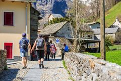 Walking on alley in Sonogno. SONOGNO, SWITZERLAND - 21 APRIL 2018 - Unidentified tourists walk on typical alleys through Sonogno village with plenty of Stock Images