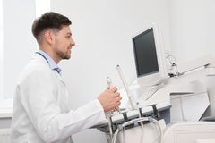 Sonographer operating modern ultrasound machine. In clinic royalty free stock photos