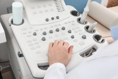 Sonographer operating modern ultrasound machine in clinic. Closeup royalty free stock image
