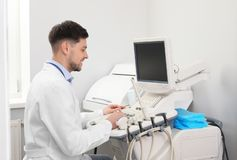 Sonographer operating modern ultrasound machine. In clinic stock photography