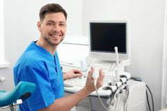 Sonographer operating modern ultrasound machine. In clinic royalty free stock photo