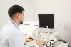 Sonographer operating modern ultrasound machine. In clinic stock photo