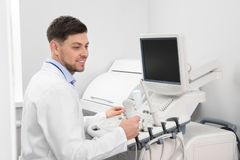 Sonographer operating modern ultrasound machine. In clinic royalty free stock images