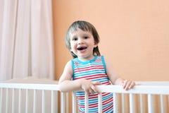 Sonriendo 2 años de niño en la cama blanca Imagenes de archivo