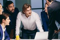 Sonriendo compañeros de trabajo masculinos femeninos y hermosos que se sientan en la tabla, mirando el ordenador portátil imagenes de archivo