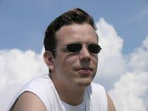Sonriendo, con las gafas de sol Fotos de archivo