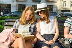 Sonriendo dos libros de lectura de las colegialas que se sientan en un banco en la ciudad Imagenes de archivo