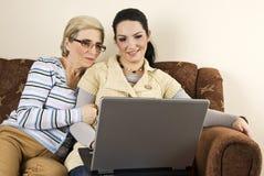 Sonriendo dos mujeres con el hogar de la computadora portátil Fotografía de archivo libre de regalías