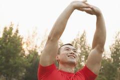 Sonriendo, los jóvenes, hombre muscular con los brazos aumentaron sobre su cabeza que estiraba en un parque en Pekín, China Imágenes de archivo libres de regalías