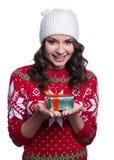 Sonriendo mujer joven bastante atractiva que lleva el suéter hecho punto colorido con la Navidad adorne y sombrero, sosteniendo e Imágenes de archivo libres de regalías