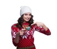 Sonriendo mujer joven bastante atractiva que lleva el suéter hecho punto colorido con la Navidad adorne y sombrero, sosteniendo e Fotos de archivo
