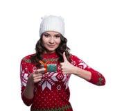 Sonriendo mujer joven bastante atractiva que lleva el suéter hecho punto colorido con la Navidad adorne y sombrero, sosteniendo e Foto de archivo libre de regalías