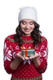 Sonriendo mujer joven bastante atractiva que lleva el suéter hecho punto colorido con la Navidad adorne y sombrero, sosteniendo e Imagen de archivo