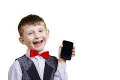 Sonriendo niño pequeño hermoso feliz, alegre que sostiene el teléfono móvil imagenes de archivo