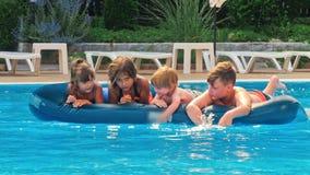 Sonriendo, niños felices en un flotador en una piscina almacen de video