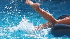 Sonriendo, niños felices en un flotador en una piscina metrajes