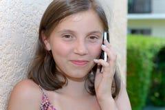 Sonriendo pre muchacha del adolescente que invita al smartphone, al aire libre Fotos de archivo