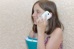 Sonriendo pre muchacha del adolescente que invita al smartphone, al aire libre Imagen de archivo libre de regalías