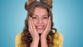Sonriendo sorprende a la chica joven hermosa en una camisa amarilla trayendo sus manos a su cara y mientras que mira en metrajes