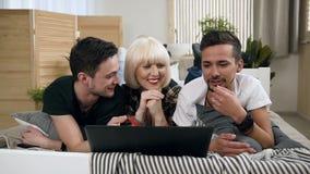 Sonriendo tres amigos que mienten junto en cama usando el ordenador portátil del ordenador mientras que es junto divirtiéndose en almacen de video