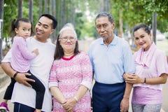 Sonriendo tres miradas de la familia de la generación en la cámara fotos de archivo