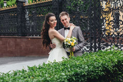 Sonriendo y abrazando a recienes casados Foto de archivo libre de regalías
