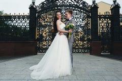 Sonriendo y abrazando a recienes casados delante de las puertas Foto de archivo libre de regalías