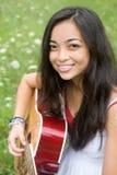 Sonriendo y tocando la guitarra Imagenes de archivo
