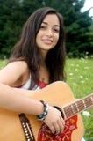 Sonriendo y tocando la guitarra Fotos de archivo