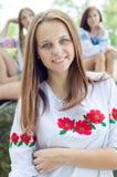 Sonriente de la chica joven hermosa y de mirada en cámara feliz en fondo del verano al aire libre Foto de archivo