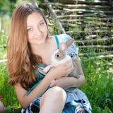 Sonriente de la muchacha feliz joven y de mirada en conejo feliz del abarcamiento de la cámara pequeño al aire libre Imágenes de archivo libres de regalías