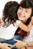 Sonrisa abrazando la mama y a la hija Foto de archivo libre de regalías