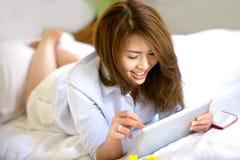 Sonrisa adolescente asiática hermosa con Ipad Imagen de archivo